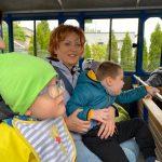 Czworo dzieci i dwie Panie siedzący w kolejce turystycznej. Dwoje dzieci siedzi u nauczycielek na kolanach.