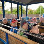 Ośmioro dzieci siedzacych w kolejce turystycznej.