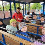 Grupa dzieci siedzących w kolejce turystycznej.