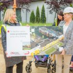 Pani Dyrektor wraz z Pania Prezydent trzymające w rękach makietę, na której widnieje wizualizacja nowego przedszkola.