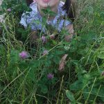 Dziewczynka leży na brzuchu na trawie