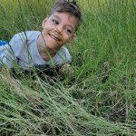 Chłopiec leży na brzuchu na trawie