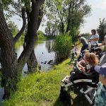 Grupa dzieci na wózkach i Pań patrza na staw i kaczki.