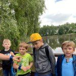 4 chłopców stoi na mostku. Za nimi widać wodę.