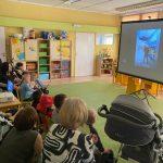 Grupa dzieci i pań siedzą na krzesłach i wózkach. Oglądają z rzutnika prezentację.