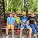 4 chłopców siedzi na ławce.