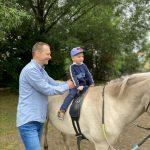 Chłopiec siedzi na koniu. Obok trzyma go tata.