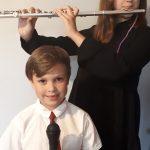 Dziewczynka grająca na flecie poprzecznym, przed którą stoi chłopiec trzymający mikrofon.