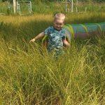 Chłopiec wychodzi z tunelu na trawie.