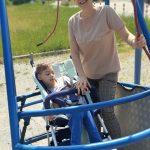 Chłopiec na wózku obok Pani huśtają się na huśtawce.