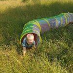 Chłopiec w tunelu na trawie.