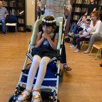 Dziewczynka na wózku z wiankiem na głowie. Za nią nauczycielka trzyma wózek.