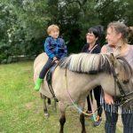 Chłopiec siedzi na koniku.Za koniem stoją 2 panie