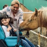 Do Dziewczynki na wózku podszedł koń. Za nią stoi Pani Dyrektor