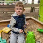 Chłopiec siedzi w piaskownicy.