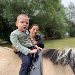 Chłopiec siedzi na koniu. Za nim trzyma go mama.