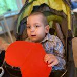 Chłopiec siedzący na wózku trzyma papierowe serduszko