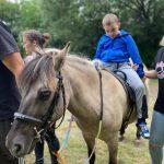 Chłopiec siedzi na koniu.