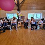 Grupa dzieci siedzi w rzędzie na krześle lub wózku. Za nimi siedzą Panie.