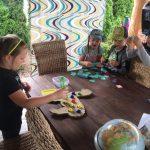 2 dziewczynki i chłopiec stoją przy stole. W rękach trzymają szczypce, którymi nakładają pompony na kontur lamy.