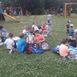 Duża grupa dzieci siedzi na kocach na trawie