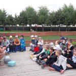 Grupa dzieci i pań siedzi na tarasie
