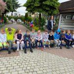 Dzieci siedzace na krzesłach w jednym rzędzie na placu przedszkolnym. Za dziećmi stoją dwie Panie.