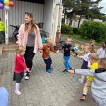 Grupa dzieci tańcząca z Panią w kole na placu przedszkola. Po lewej stronie widocznych jest tańczących sześcioro dzieci.