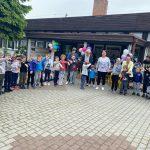 Dzieci wraz z pięcioma Paniami stojacy w półkolu przed budynkim przedszkola.