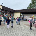 Grupa dzieci tańczących w parach przed budynkiem przedszkola, który jest udekorowany kolorowymi balonami i wiatrakami.