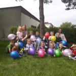 Grupa dzieci pozujaca do zdjęcia w ogrodzie przedszkolnym i trzymajaca w rękach kolorowe balony. Z dziećmi siedzą dwie Panie.