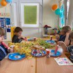 Czterech chłopców siedzących przy stolikach w sali przedszkolanej i jedzących lody. Stoły udekorowane są kolorowymi wstążkami.