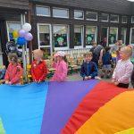 Sześcioro dzieci będących na placu przedszkola i trzymających kolorowąchustę. W tle widoczna jest Pani wraz z dziećmi trzynającymi drugą, kolorową chustę.