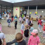 Dzieci tańczące na placu przed przedszkolem, który udekorowany jest balonami i wiatrakami.
