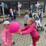 Dwie dziewcznki łapiące różowy balon na placu przedszkola. W tle widać dzieci oraz Panią trzymającą wózek, w którym siedzi dziewczynka.