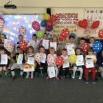 Grupa dzieci pozujaca do zdjęcia w dwóch rzędach w sali przedszkolnej. Dzieci w pierwszym rzędzie siedza na krzesłach, w drugim rzędzie stoją.Dzieci trzymają w rękach balony i dyplomy.