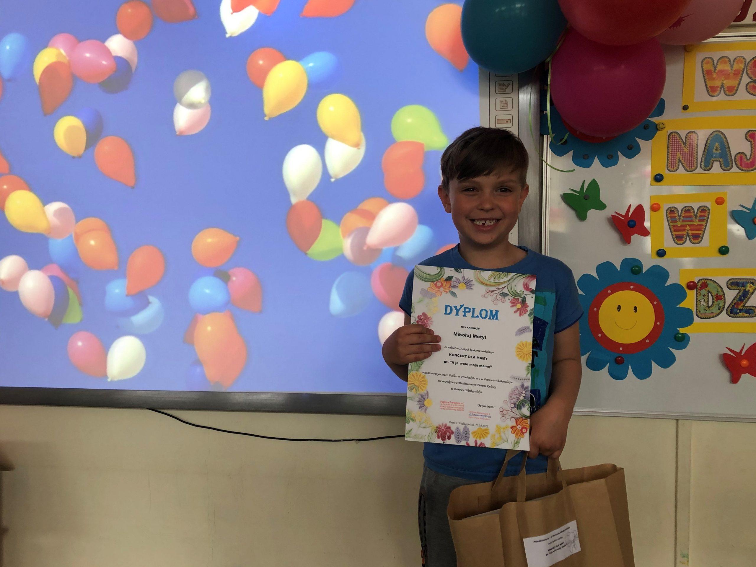 Chłopiec trzymajacy dyplom oraz nagrodę. W tle zdjęcia widać kolorowe balony.