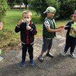 Czworo dzieci będąvcych w ogrodzie przedszkolnym. Dwóch chłopców puszcza bańki mydlane.