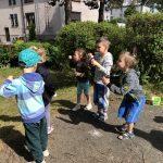 Pięcioro dzieci puszczających w ogrodzie przedszkolnym bańki mydlane.