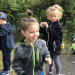 Czworo dzieci znajdujących się w ogrodzie przedszkolnym. Chłopiec i dziewczynka puszczaja bańki mydlane.