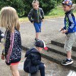 Dwoje dzieci rysujących kredą po asfalcie. Troje pozostałych dzieci stoi i patrzy.