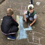 Dwóch chłopców rysujących kredą po asfalcie.