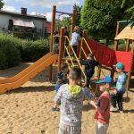 Grupa dzieci bawiących się na placu zabaw.