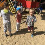 Grupa dzieci biegających po placu zabaw. Jeden chłopiec trzyma w ręku pojemnik do baniek mydlanych.