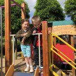 Chłopiec i dziewczynka stoją na drewnianym domku, na placu zabaw.