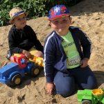 Dwóch chłopców siedzi na piasku na placu zabaw. Przed każdym z nich znajduje się autko.