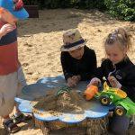 Chłopiec i dziewczynka kucają przy stoliku na placu zabaw. Na stoliku znajduje się autko i piasek. Po lewej stronie stoi chłopiec.