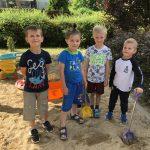 Czterch chłopców stoi na placu zabaw i trzyma w rękach łopatki.