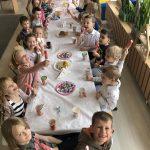 Grupa dzieci siedzacych przy wspólnym stole w sali przedszkolnej i trzymająca lody. Stół udekorowany jest balonami.