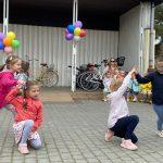 Cztery dziewczynki tańczące w parach na placu przedszkola. W tle widoczna jest Pani i dzieci siedzace na krzesłach.